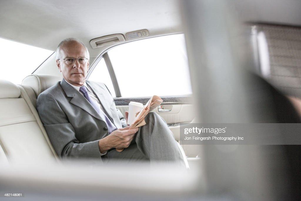 Caucasian businessman reading newspaper in car : Stock Photo