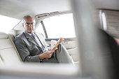 Caucasian businessman reading newspaper in car