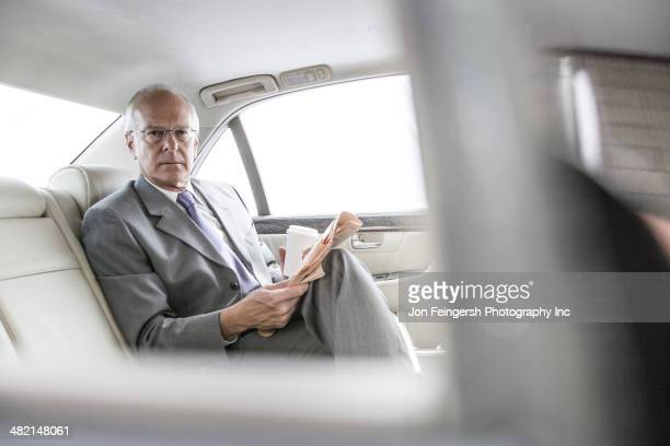 Caucasian businessman reading newspaper in car