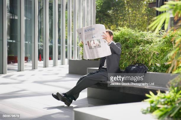 Caucasian businessman reading newspaper in urban park