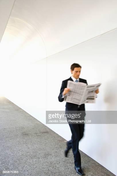 Caucasian businessman reading newspaper while walking