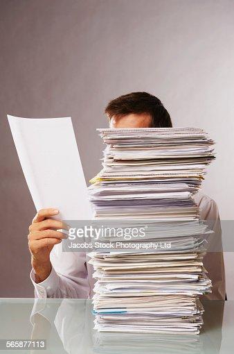 Caucasian businessman reading stack of paperwork