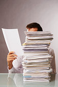 Caucasian businessman reading stack of paperwork