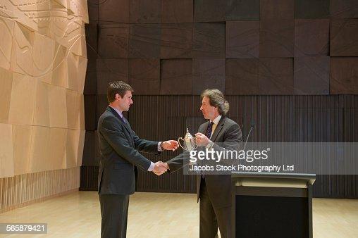 Caucasian businessman receiving trophy and handshake