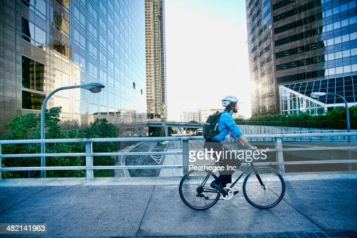 Caucasian businessman riding bicycle on urban street