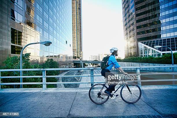 Caucasian businessman riding bicycle on urban street