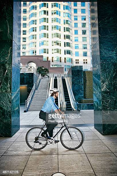 Caucasian businessman riding bicycle outside highrise