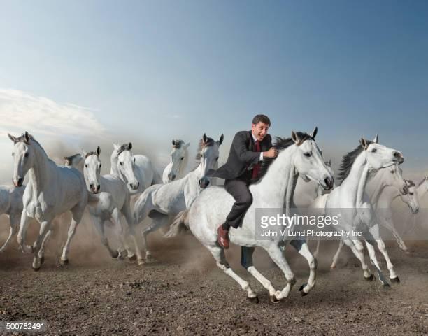 Caucasian businessman riding wild horse in desert