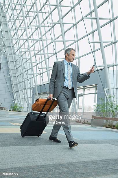 Caucasian businessman rolling luggage in lobby