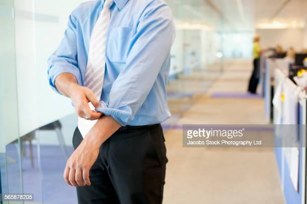 Caucasian businessman rolling up sleeves in office