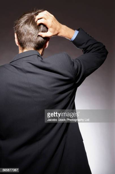 Caucasian businessman scratching his head
