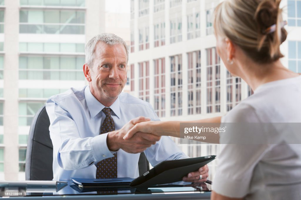 Caucasian businessman shaking hands with client : Stock Photo