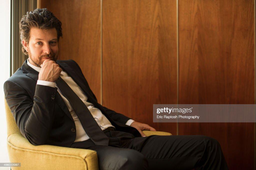 Caucasian businessman sitting in armchair : Stock Photo