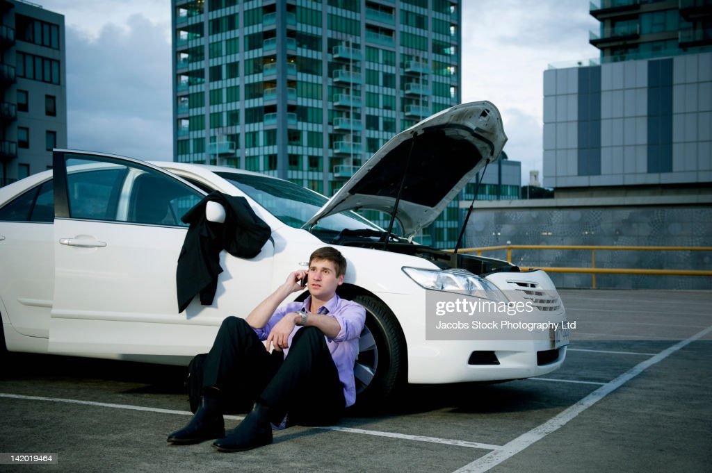Caucasian businessman sitting near car having car trouble
