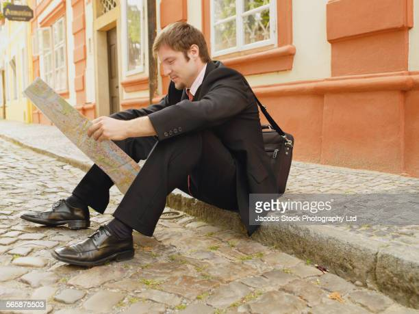 Caucasian businessman sitting on city curb reading newspaper
