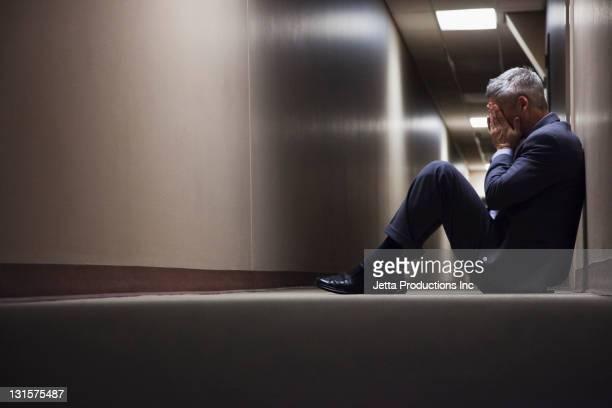Caucasiano Empresário sentado no chão no corredor