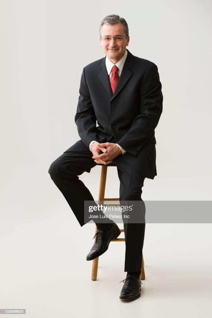 Caucasian businessman sitting on stool