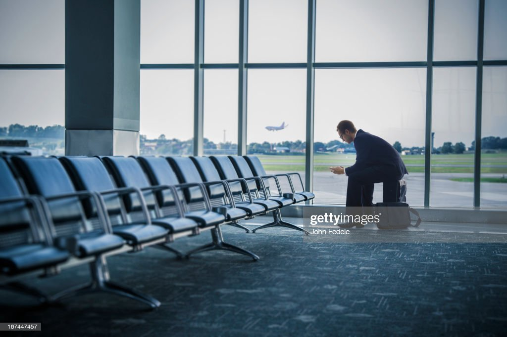 Caucasian businessman sitting suitcase in airport : Stock Photo