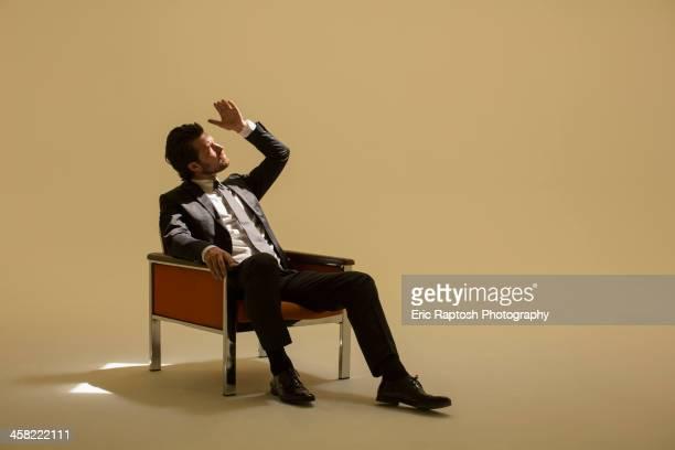 Caucasian businessman sitting under spotlight