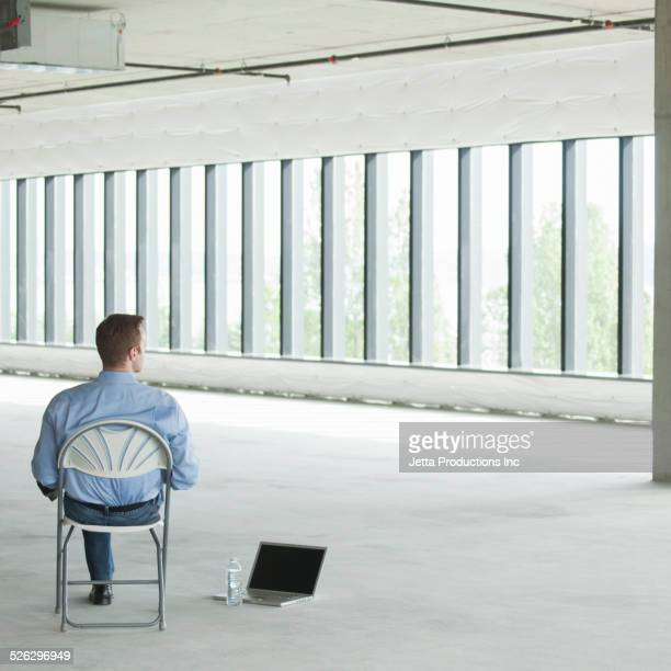 Caucasian businessman sitting with laptop on floor