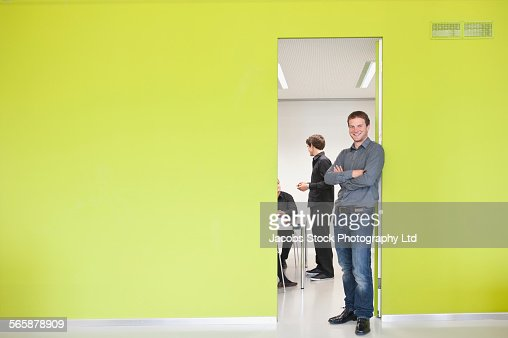 Caucasian businessman smiling at door to office meeting