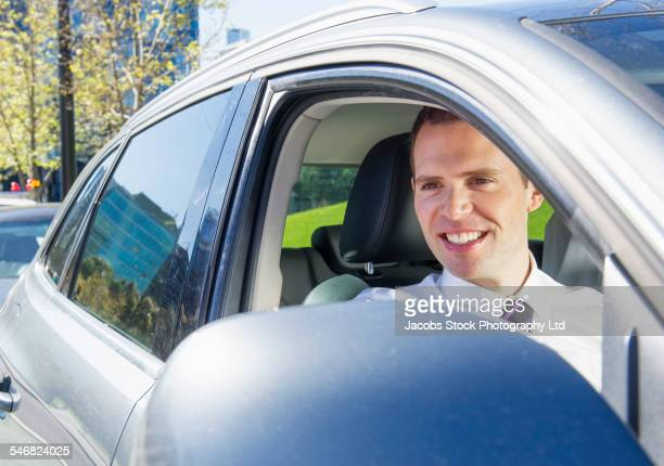 Caucasian businessman smiling in car window