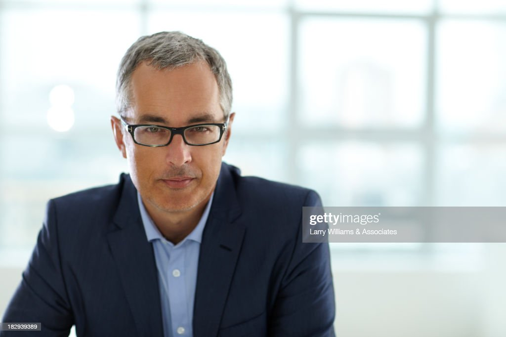 Caucasian businessman smiling in office : Stock Photo