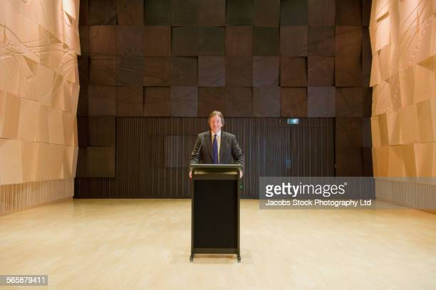 Caucasian businessman standing at podium on stage