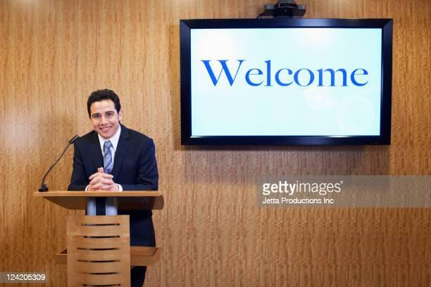 Caucasian businessman standing at podium