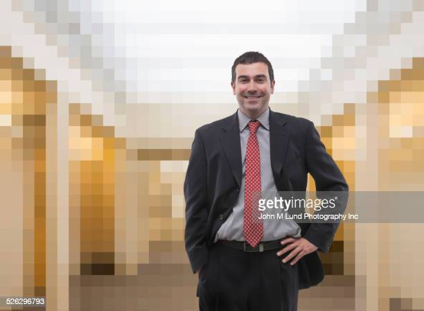 Caucasian businessman standing in pixelated office lobby