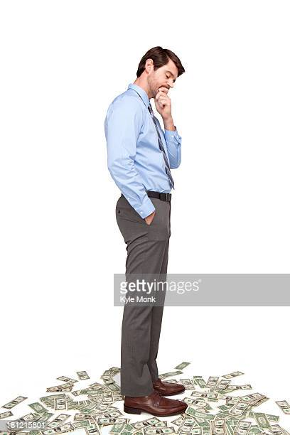 Caucasian businessman standing on money