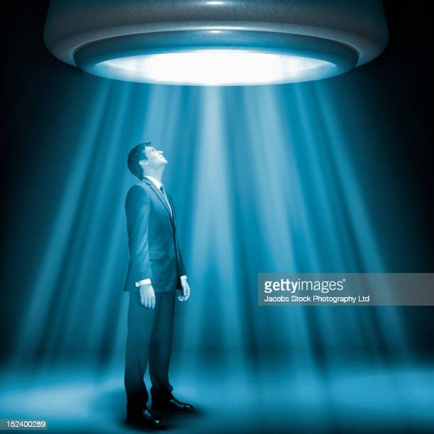 Caucasian businessman standing underneath glowing lights