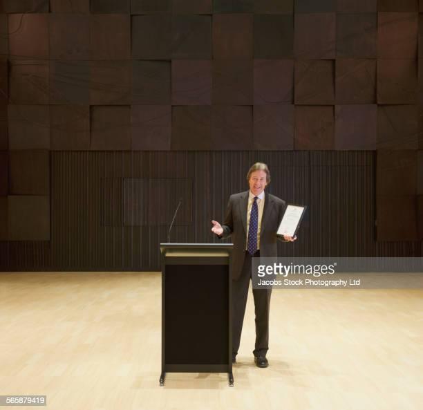Caucasian businessman talking at podium on stage