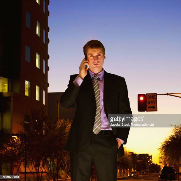 Caucasian businessman talking on cell phone at sunset