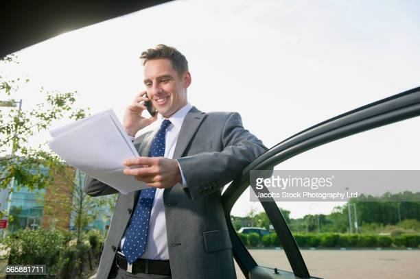 Caucasian businessman talking on cell phone cell phone near car