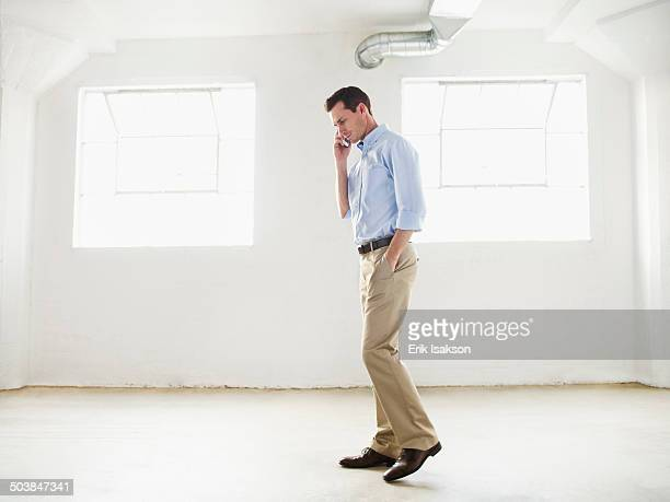 Caucasian businessman talking on cell phone in empty office