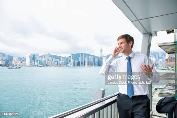 Caucasian businessman talking on cell phone on balcony