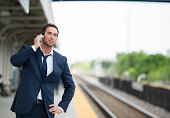 Caucasian businessman talking on cell phone on train platform