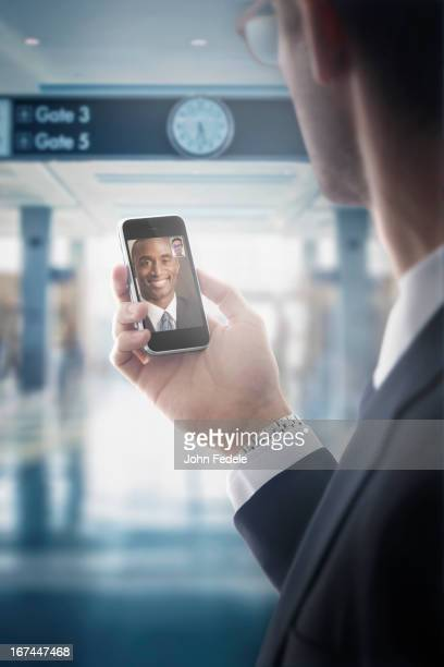 Caucasian businessman text messaging on cell phone in airport
