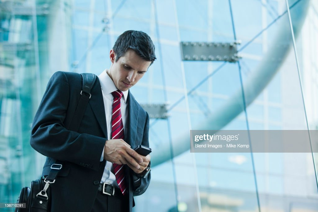 Caucasian businessman text messaging on cell phone outdoors : Stock Photo