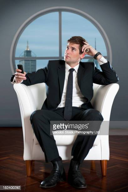 Caucasian businessman text messaging on cell phone