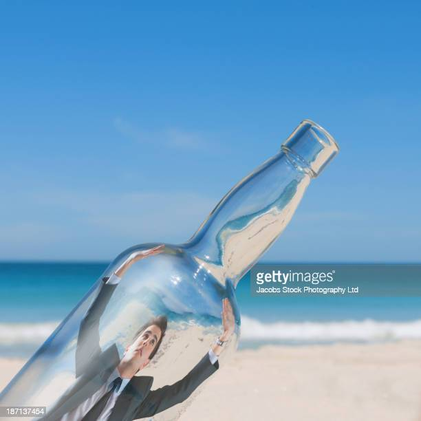 Caucasian businessman trapped in glass bottle on beach