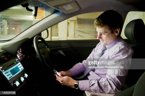 Caucasian businessman using cell phone in car