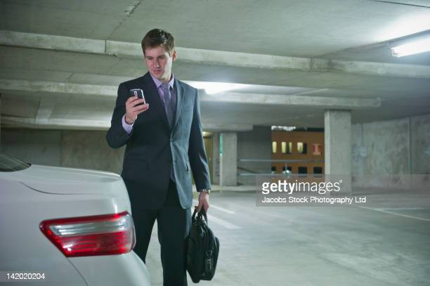 Caucasian businessman using cell phone in parking garage