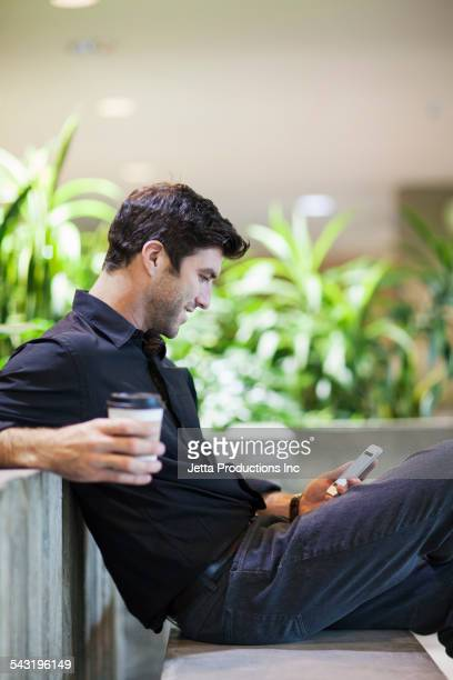 Caucasian businessman using cell phone on bench