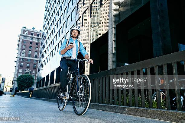 Caucasian businessman using cell phone on bicycle
