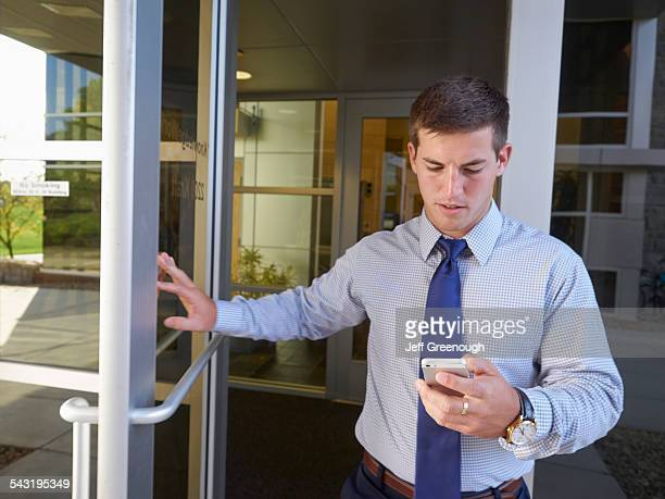 Caucasian businessman using cell phone outside office building