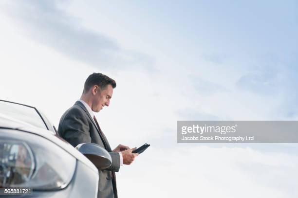 Caucasian businessman using digital tablet near car