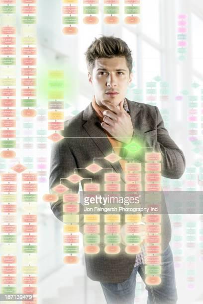 Caucasian businessman using illuminated touch screen