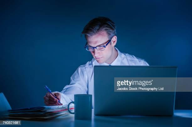 Caucasian businessman using laptop and reading paperwork